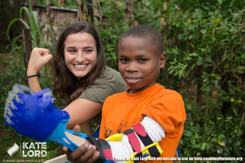 Amos, a student at Arlington Academy of Hope in Bududa district of Uganda, receives a prothetic arm that was 3D printed for him at Marymount University. Amos poses with Danielle Fortin, Arlington Academy of Hope's International Coordinator. (photo by Kate Lord)