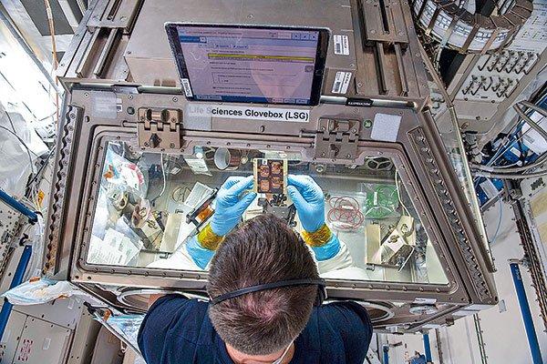 Astronaut at NASA's ISS testing 3D printing materials.